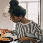 [Image Description: Woman with messy bun eating noodles out of a pan.] Via Pexels
