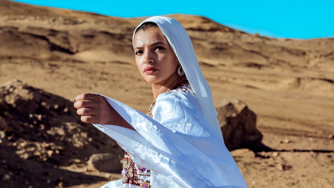 [Image Description: Woman in scarf and traditional clothing against a desert backdrop. Via Pexels]