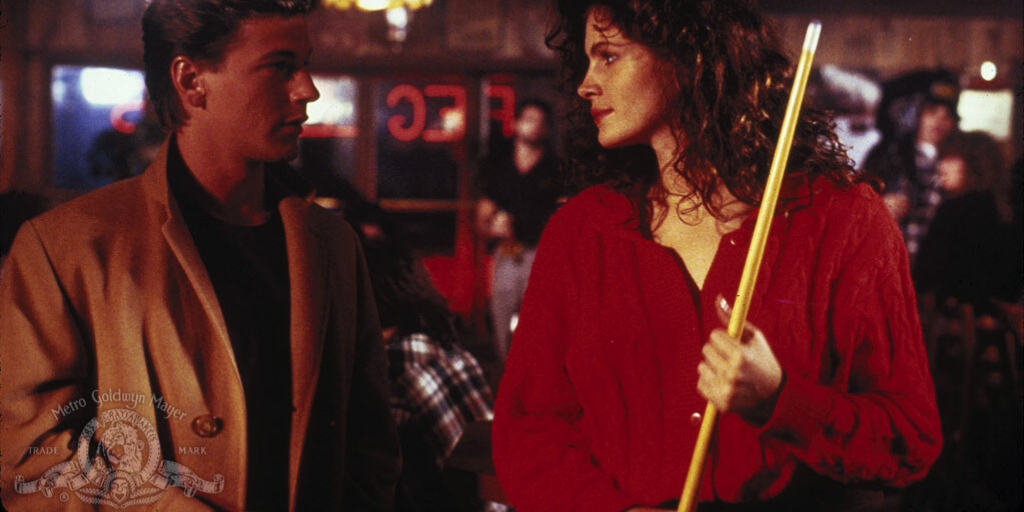 Still from 'Mystic Pizza' (1988). A curly-haired woman in a red sweater holding a pool cue looks over at a man wearing a tan jacket.