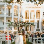 [Image Description: A couple getting just married kissing in front of a restored plantation house.] via Nottoway Plantation