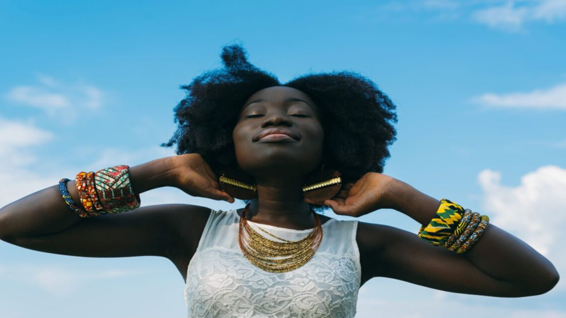 A black girl wearing a sleeveless white top and colorful bangles has her eyes eyes closed and is facing up to the blue sky.