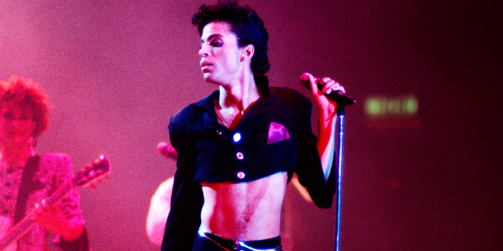 Prince performs on stage wearing a long-sleeved, collared crop top.