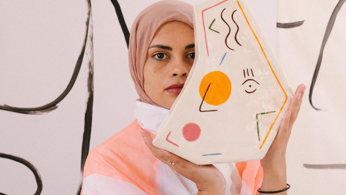 [Image Description: A woman wearing a hijab holds an abstract vase in a studio. Via Pexels]