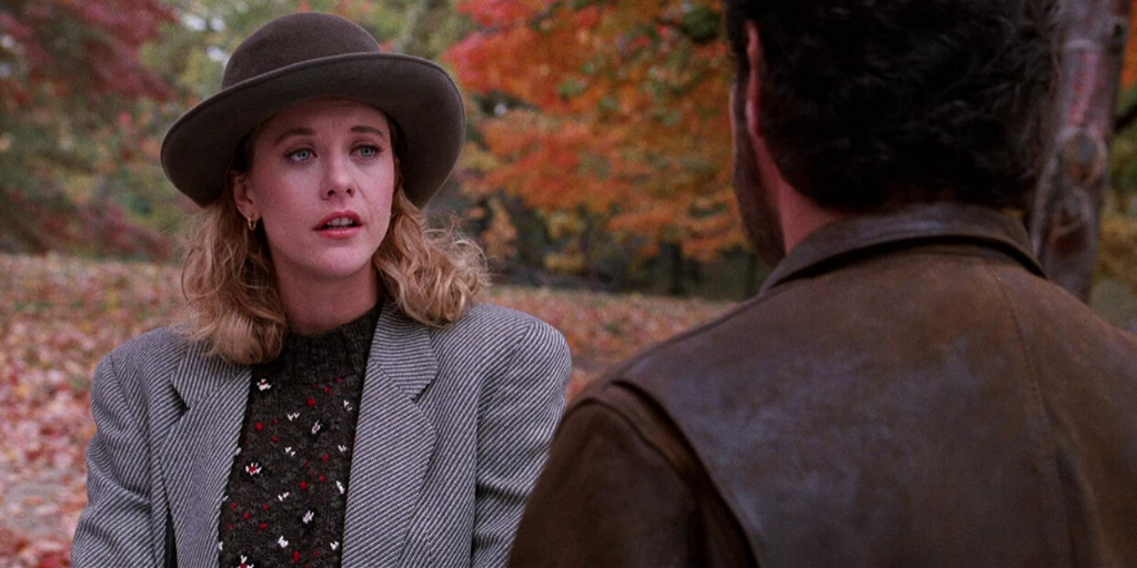 Still from 'When Harry Met Sally' (1989). A blonde woman wears a striped jacket, patterned sweater, and bowler hat in a park.