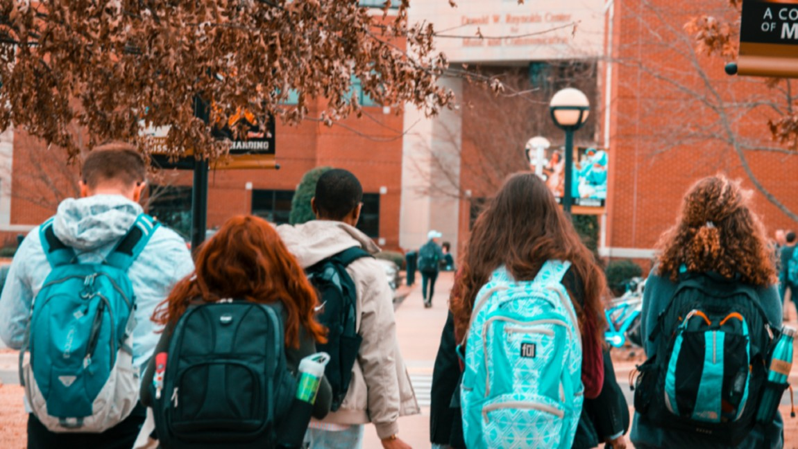 [Image Description: Students with backpacks walking toward a school building.] Via Pexels