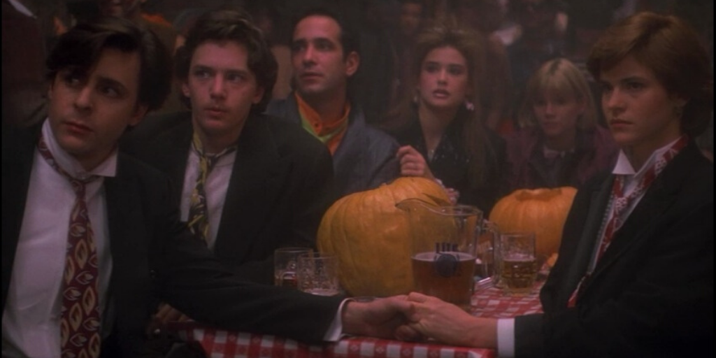 Still from 'St.Elmo's Fire' (1985). A group of young men and women sit at a table with pumpkins and drinks scattered between them.