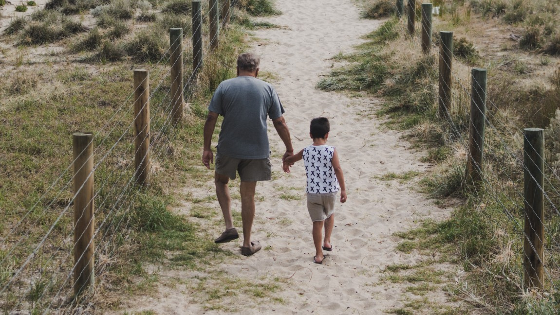 A grandfather walks along a strip of sand, holding the hand of his grandchild. Via Unsplash.