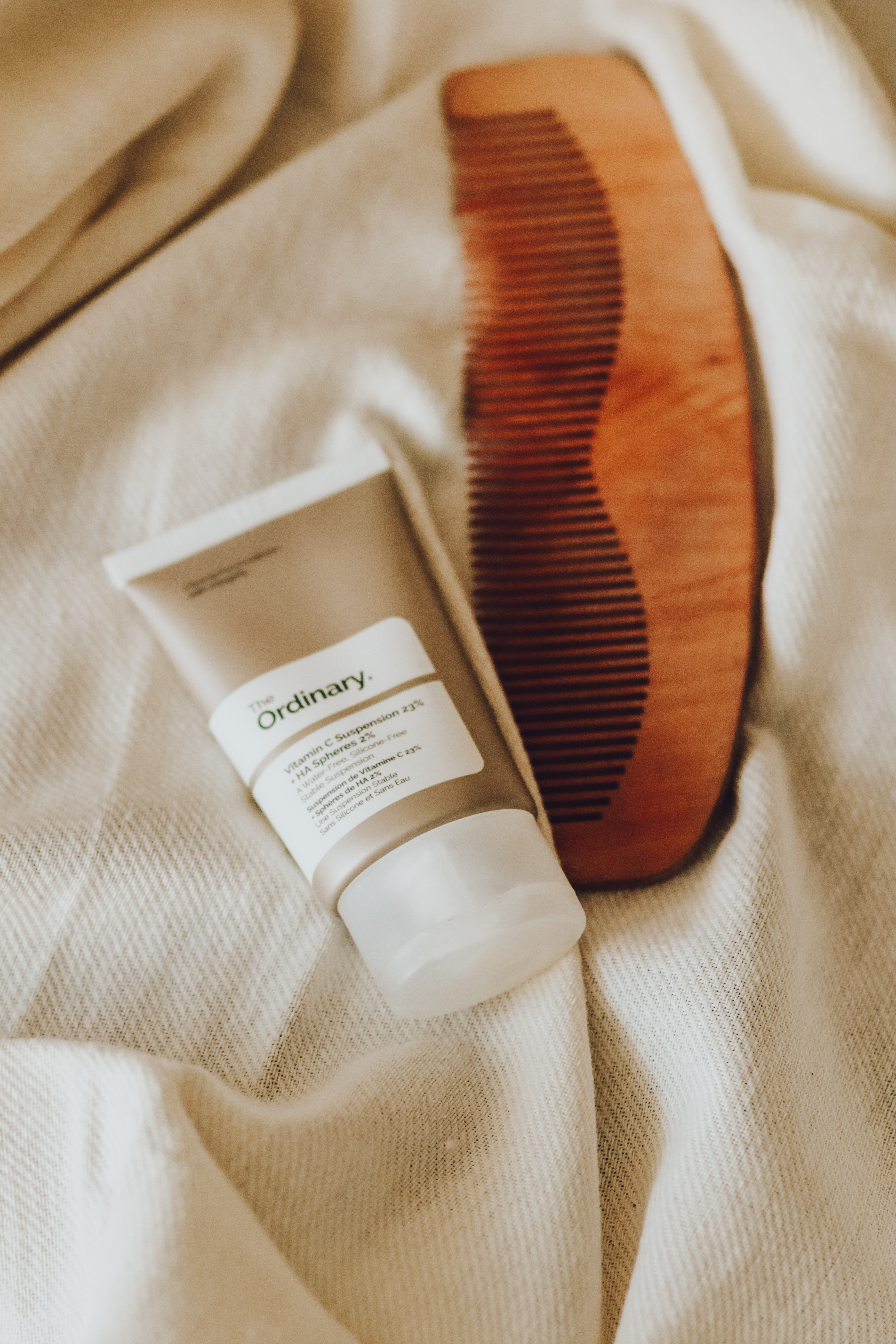 A tube of The Ordinary's Vitamin C Suspension is placed on a bed at a slight angle. Next to it is a brown comb.