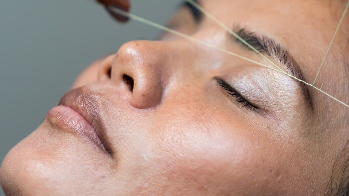 A woman lying down with her eyes closed, while another woman threads her eyebrow.