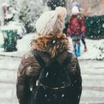 A person stands on the side of a wintry street.