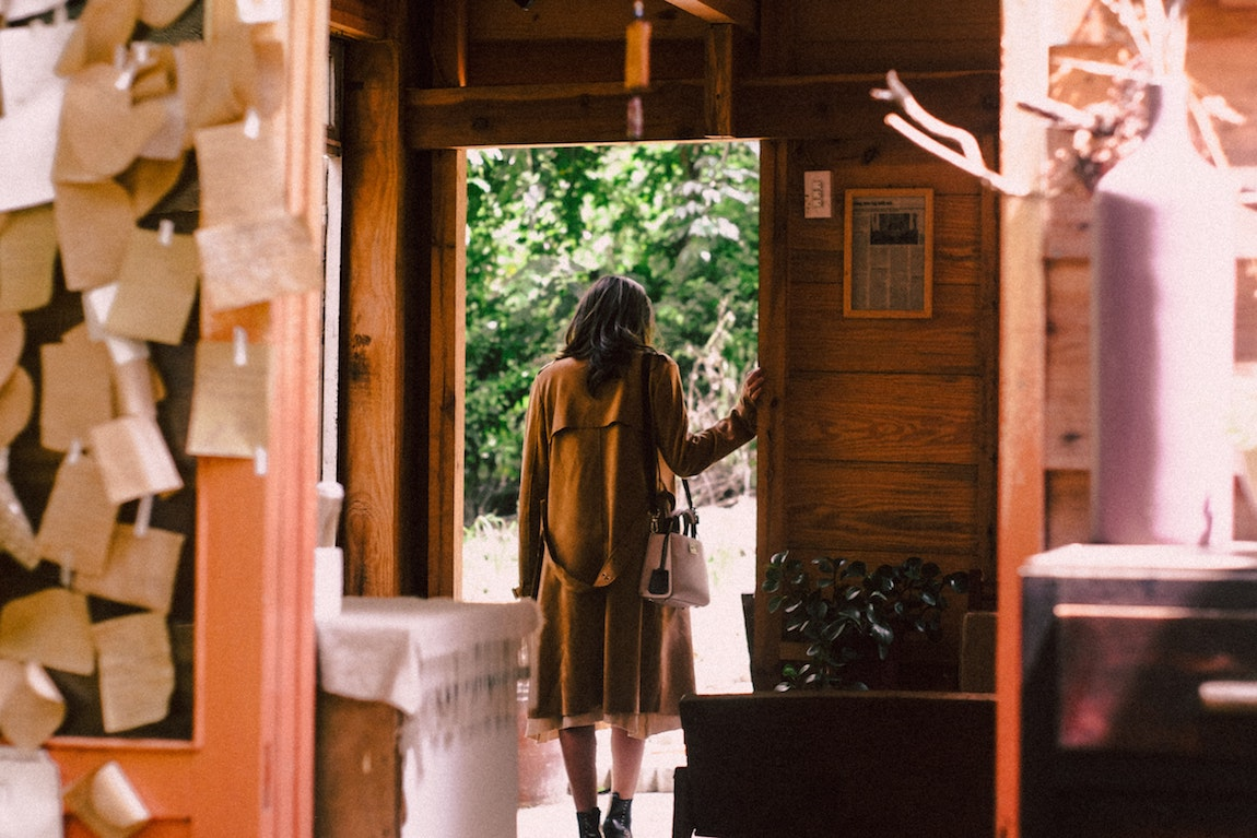 [Image Description: Woman standing near an open door, about to step outside.] Via Pexels.