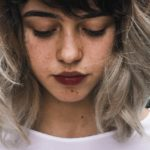 [Image description: A young woman with gray ombre hair, spots on her cheeks and dark lipstick looks down wistfully.] Via Pexels