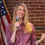 [Image Description: Senator Kelly Loeffler, a woman with long blonde hair, is dressed in a pink plaid shirt and holding a microphone up to her face while standing in front of a brick wall and an American flag]. Via Kelly Loeffer / Twitter.