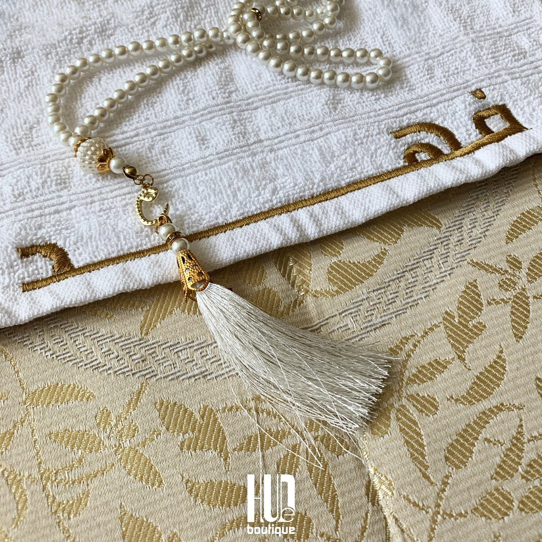 [Image description: A customized golden prayer mat and Wudhu Towel with the name 'Fahad' embroidered on, as well as prayer beads. ] Via HuDeBoutique.