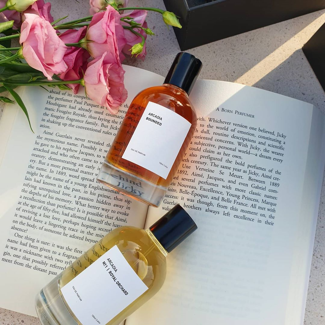 Two bottles of perfume on a book next to pink roses