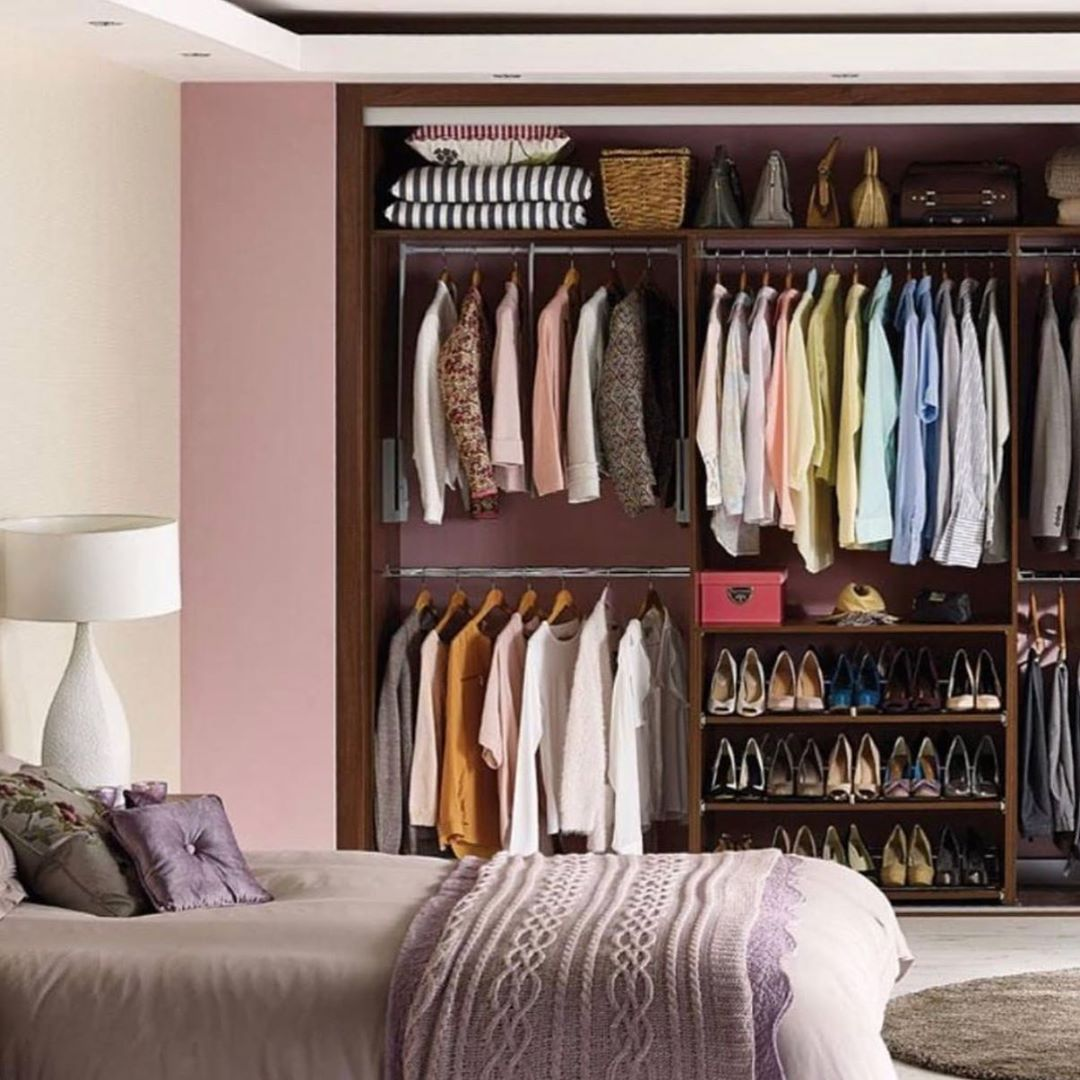 There is a bed behind which there is a bedside table with a lamp and a closet that shows neatly arranged shirts hanging up, towels folded, a hamper, and shoes and handbags lined up on the shelves.
