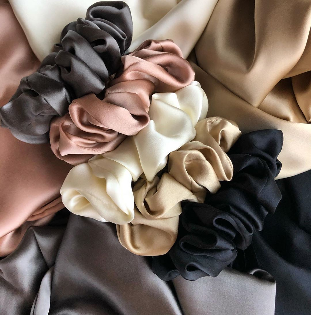 Three silk scrunchies in beige tones against silk pillowcases.