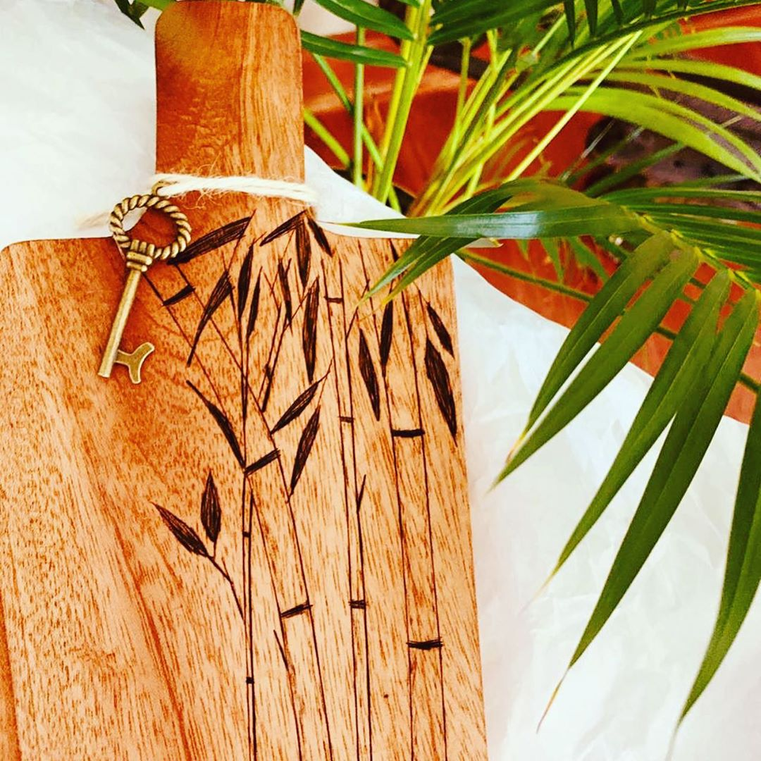 [Image description: A wooden cheeseboard with bamboo designs. A key is tied around its handle and there are plants in the background.