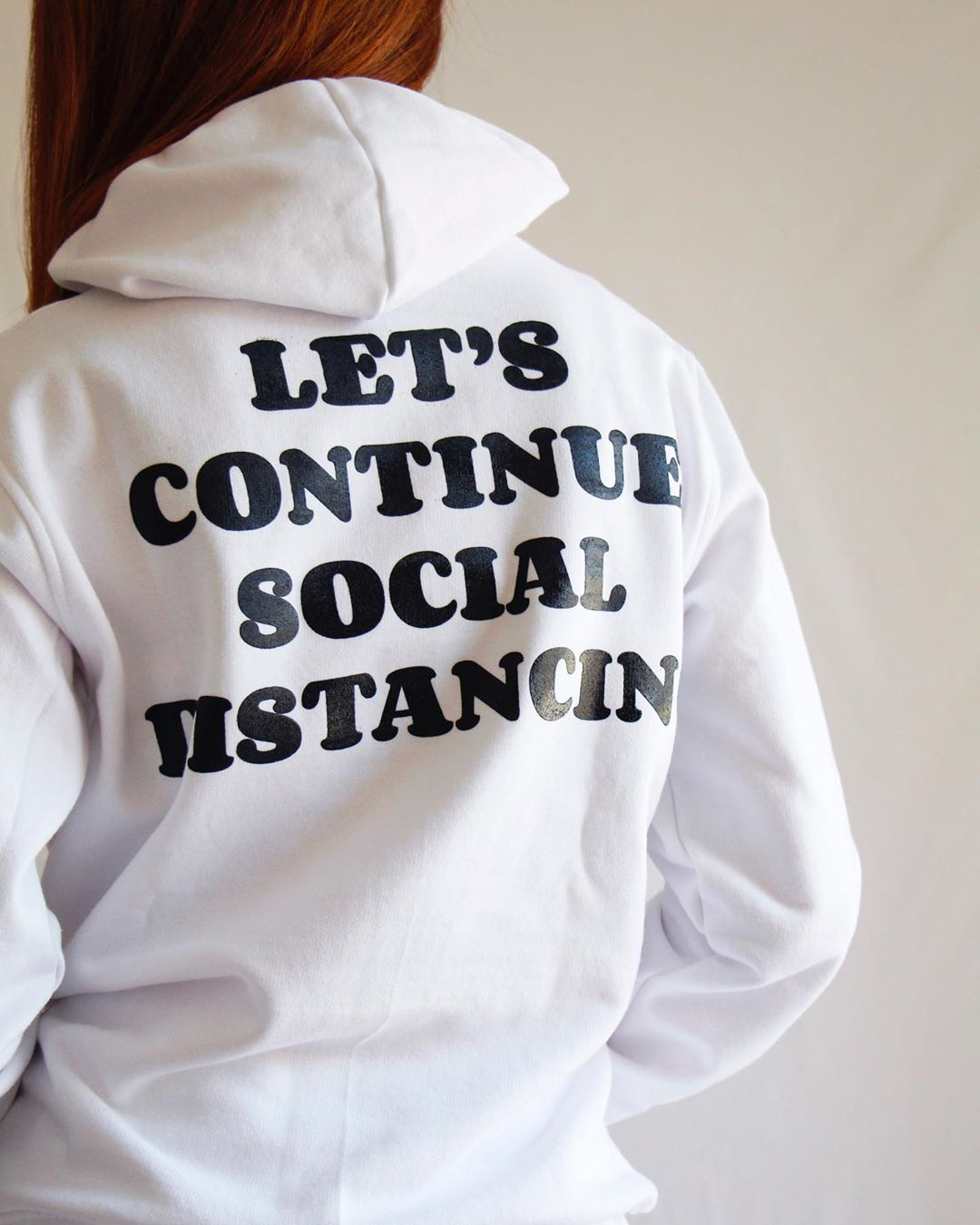 A woman wears a white hoodie with the words 'Let's continue social distancing' in black lettering on the back.