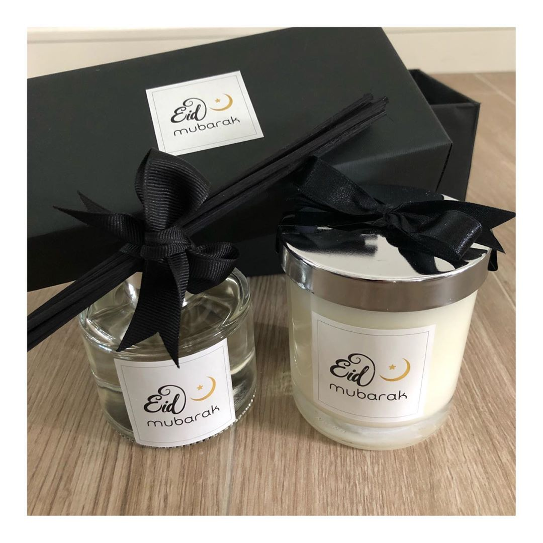 A soy wax candle wrapped in a black bow beside a reed defuser also tied with a black bow. Both are on a wooden table and behind them is the black gift box.