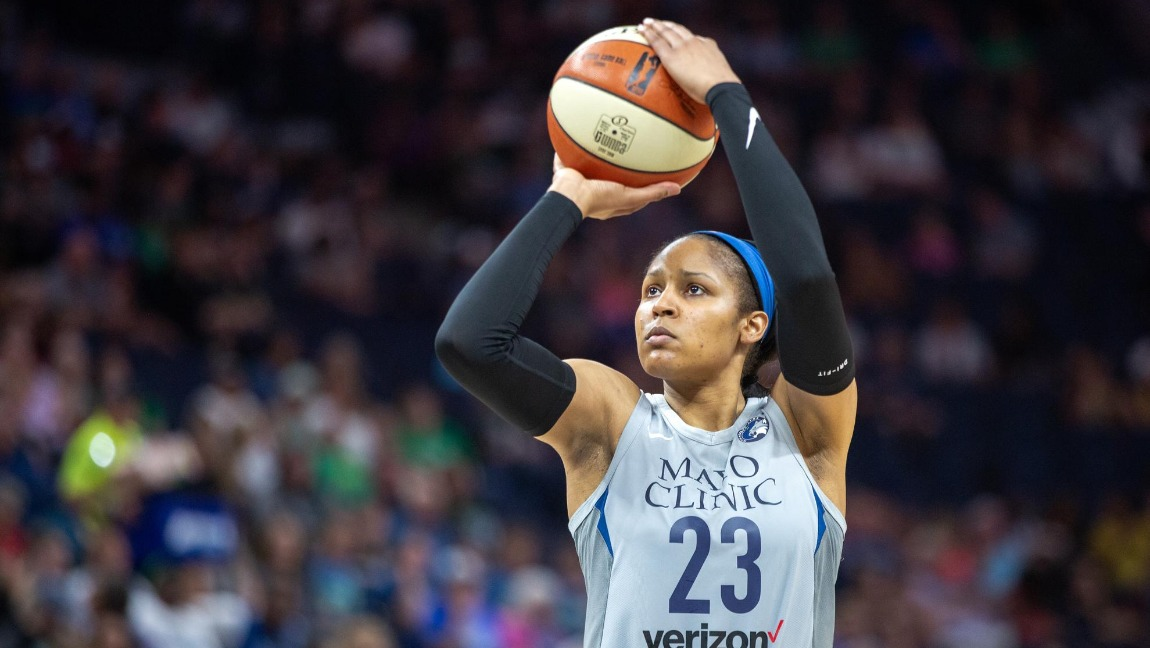 "[Image Description: Maya Moore, wearing black sleeves and her grey-blue Minnesota Lynx uniform with ""Mayo Clinic"" written on the front, holds a basketball up as she lines up to take a shot]. Via Lorie Shall / Wikimedia Commons."