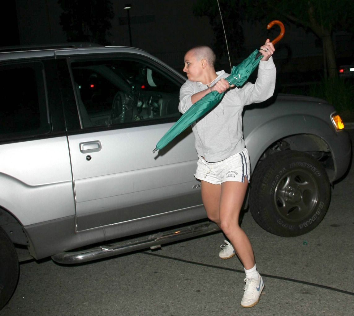 Britney spears attacking a silver paparazzi vehicle with a green umbrella.