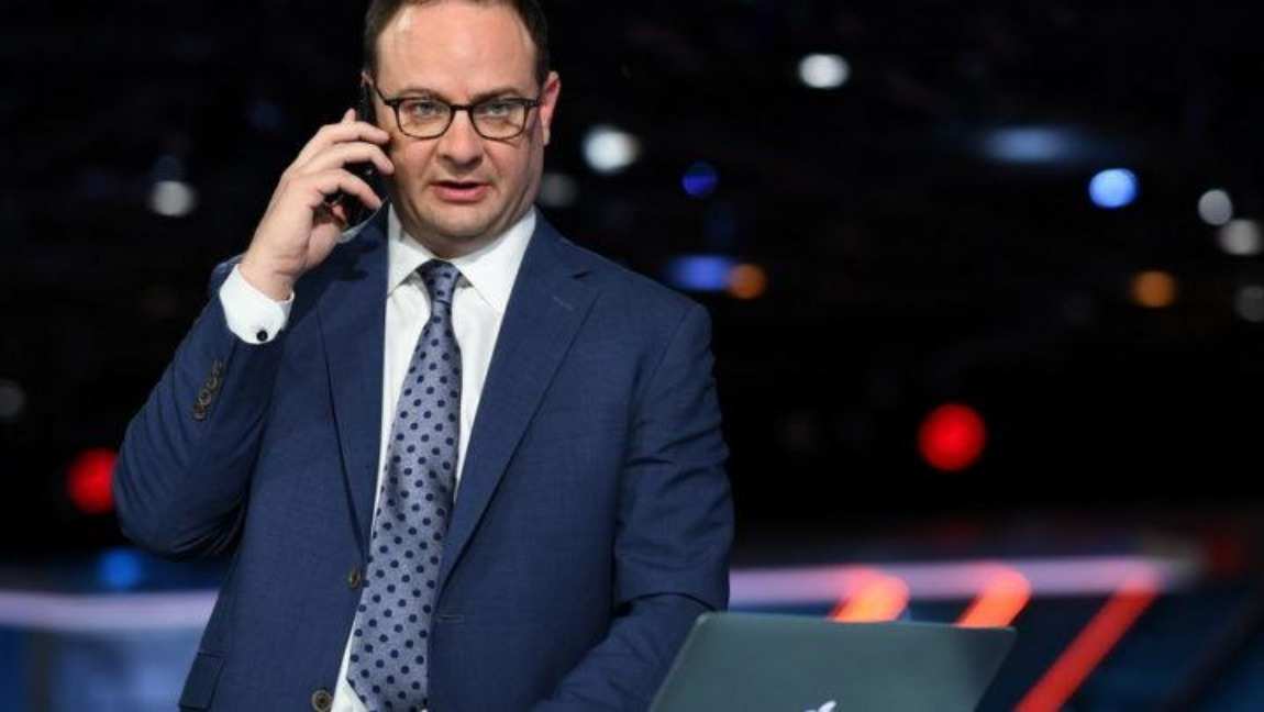 [Image Description: Woj sits at a desk, dressed in dark suit and tie and holding a phone to his ear]. Via ESPN Press Room.