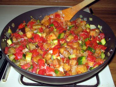 A saucepan and wooden spatula in the process of cooking zucchini, tomato, and potato