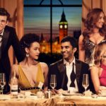 "Main cast and character feature photo of Hulu's ""Four Weddings and a Funeral"" where they are all sitting at a table set with drinks and plates."