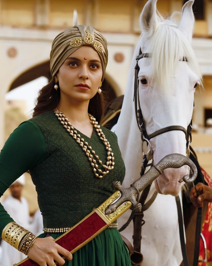 A still from the movie Manikarnika: The Queen of Jhansi. A woman, the queen of Jhansi, wearing a turban. She is holding a sword in one hand as she stares in the distance. A white horse is standing beside her.