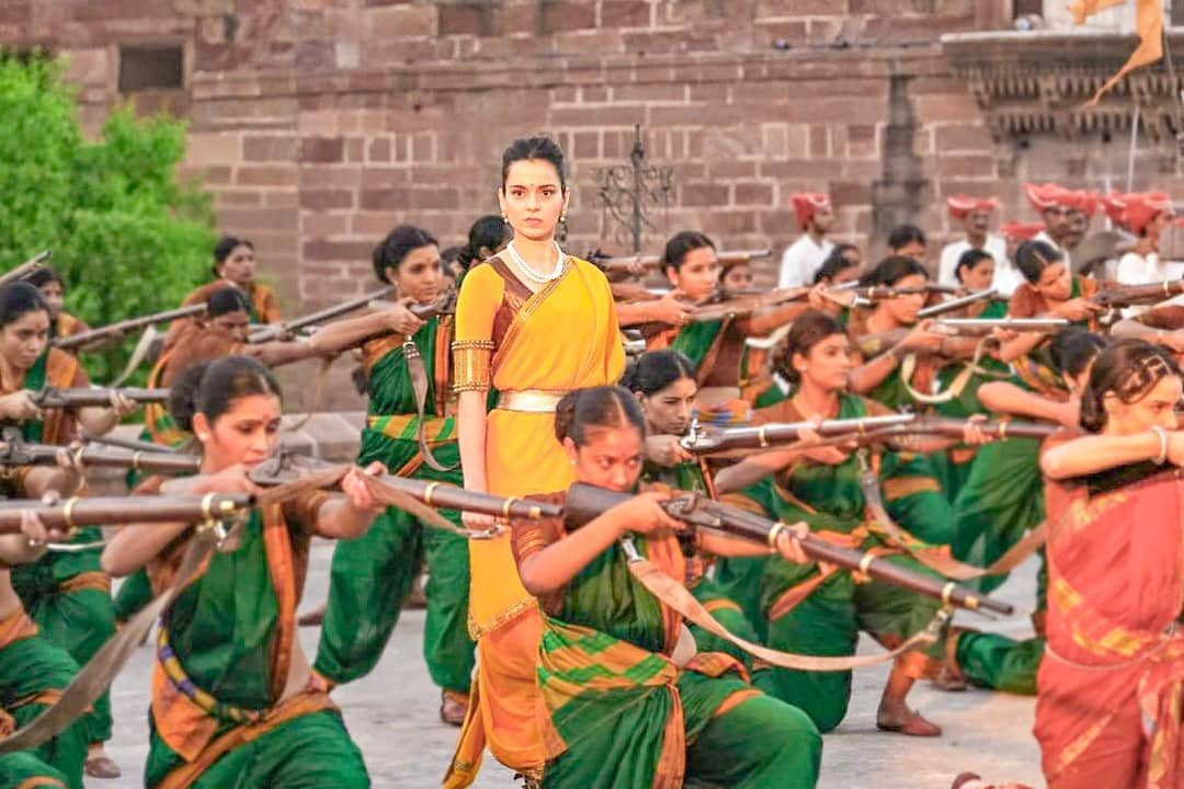 A still from the movie Manikarnika: The Queen of Jhansi. A woman, the queen of Jhansi, stands in the middle wearing a yellow sari. She is surrounded women in green saris, kneeling on the ground holding guns.