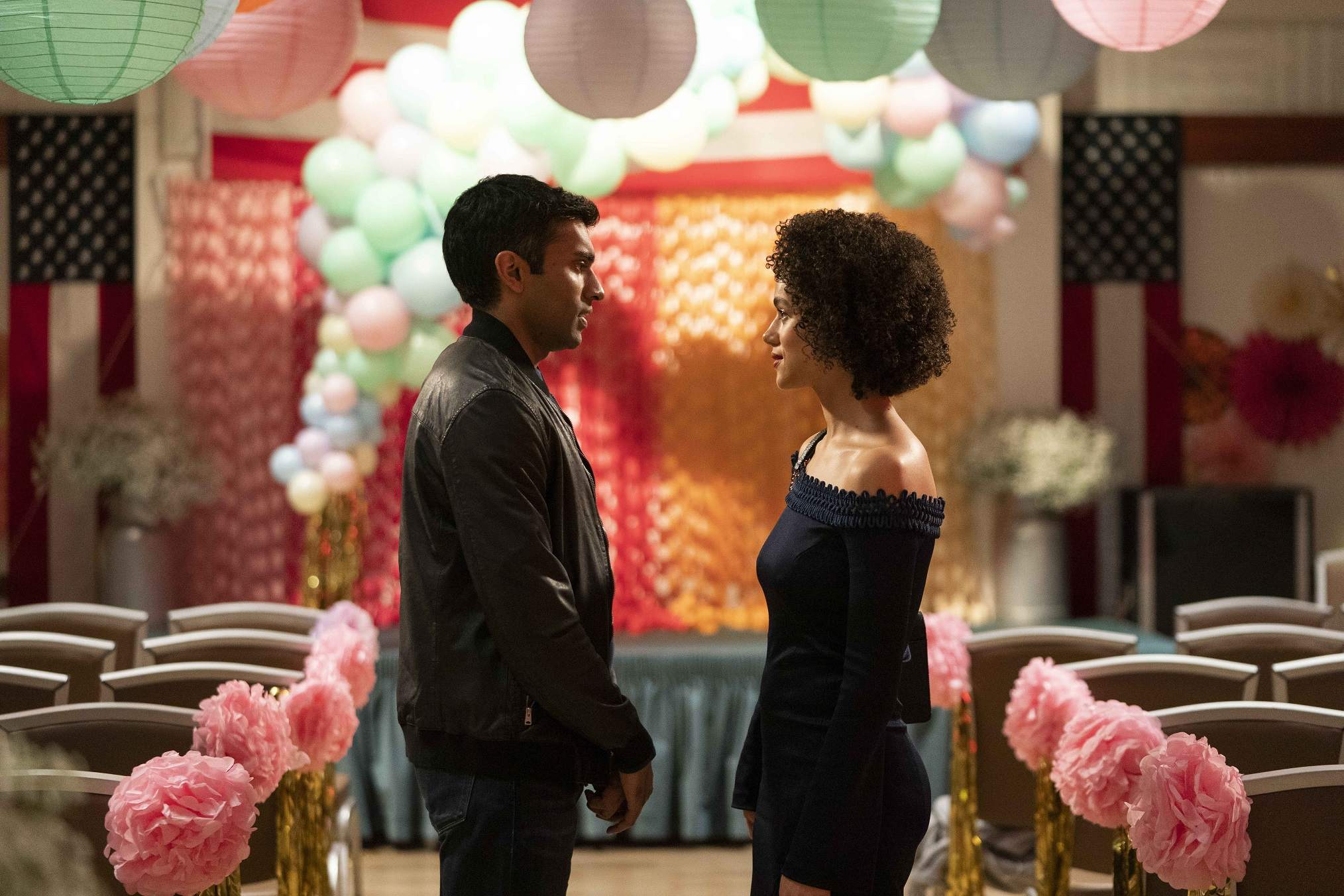 """Maya (Nathalie Emmanuel) and Kash (Nikesh Patel) of the """"Four Weddings and Funeral"""" reboot facing each other in a decorated wedding hall."""