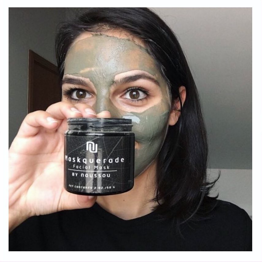 A woman wearing the Maskquerade Facial Mask holds up the black tub of Noussou product.