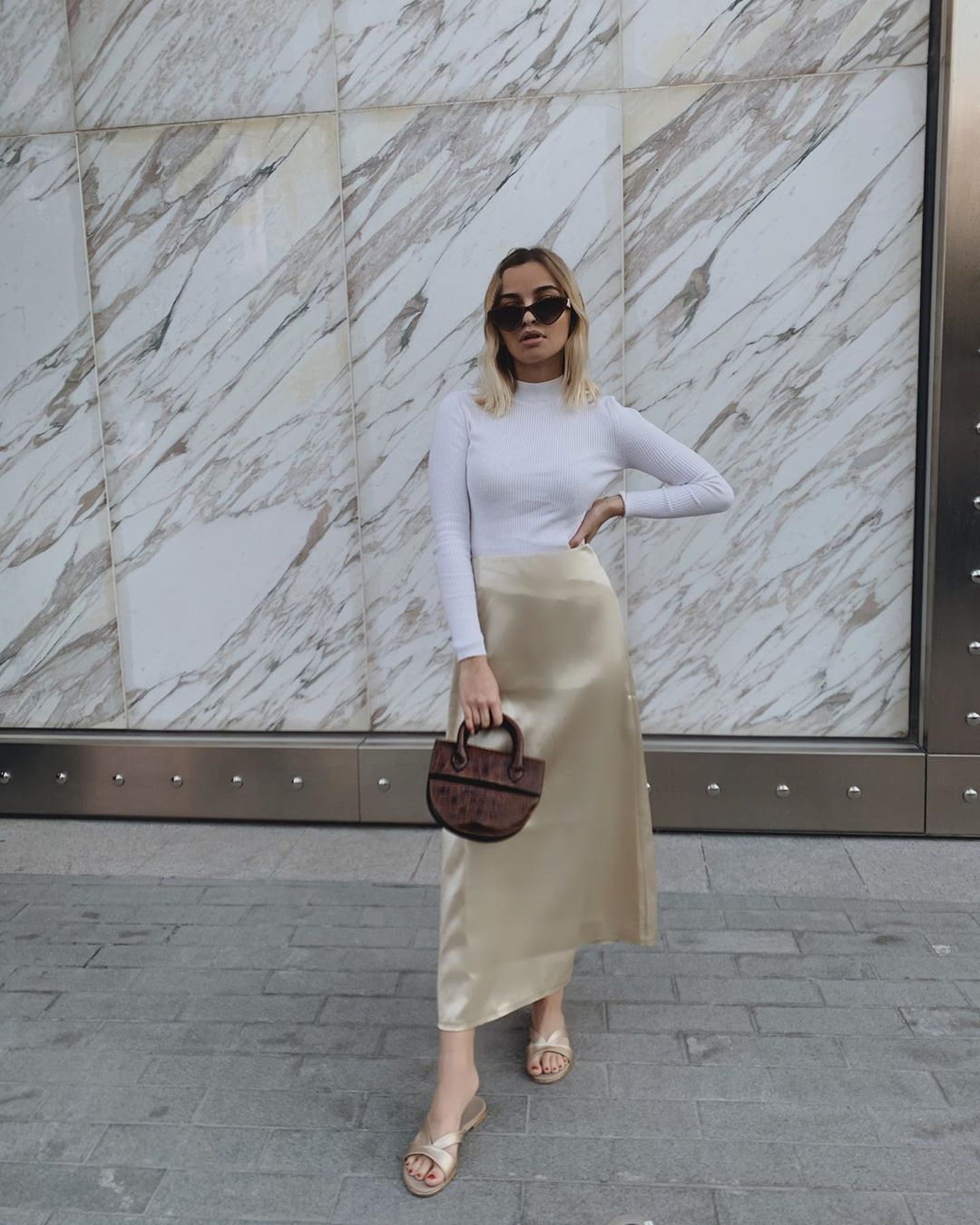 A woman in a white turtleneck and satin skirt holding a burgundy croc exterior semi-circle handbag.
