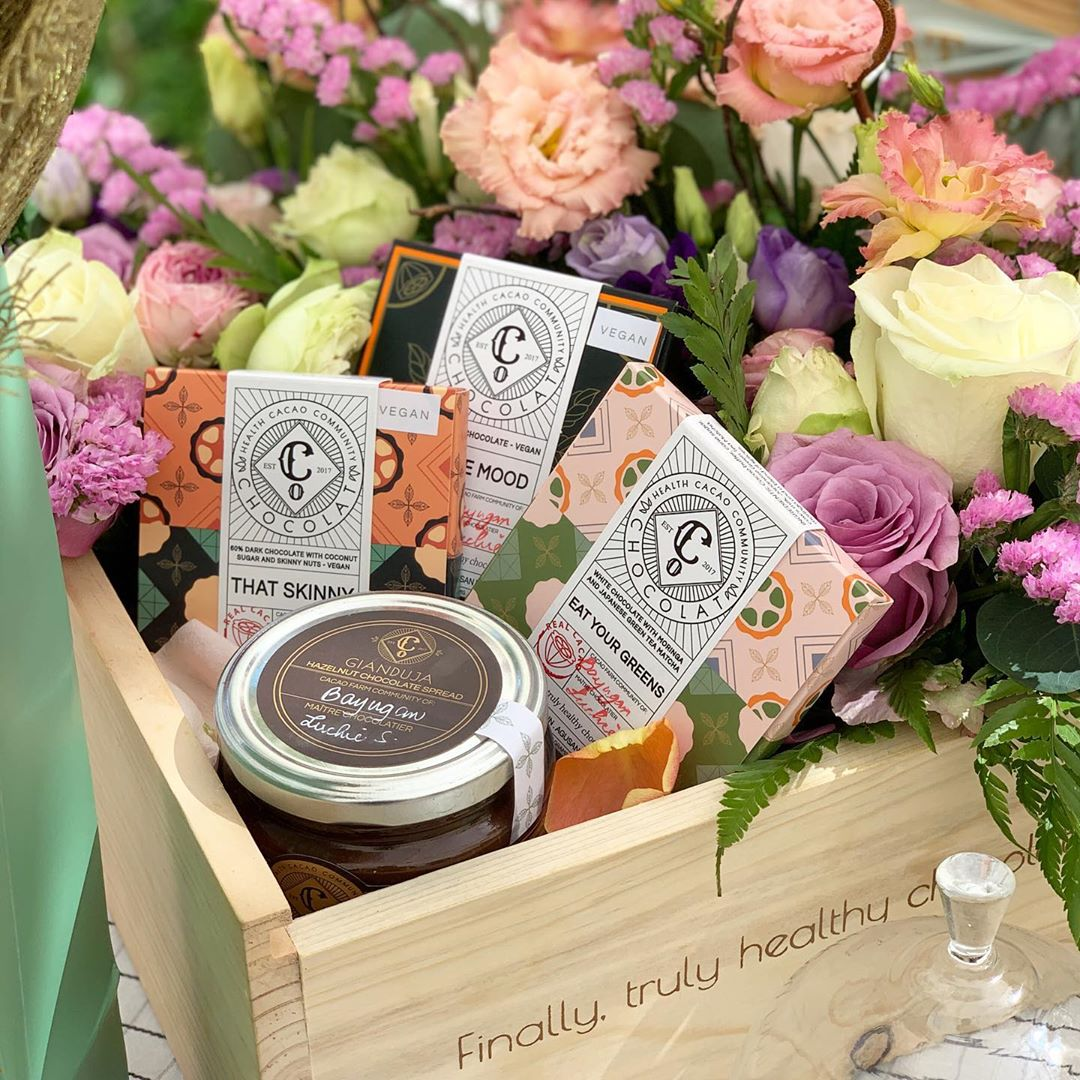 A selection of chocolate bars and a jar of Gianduja spread displayed in a crate full of flowers.