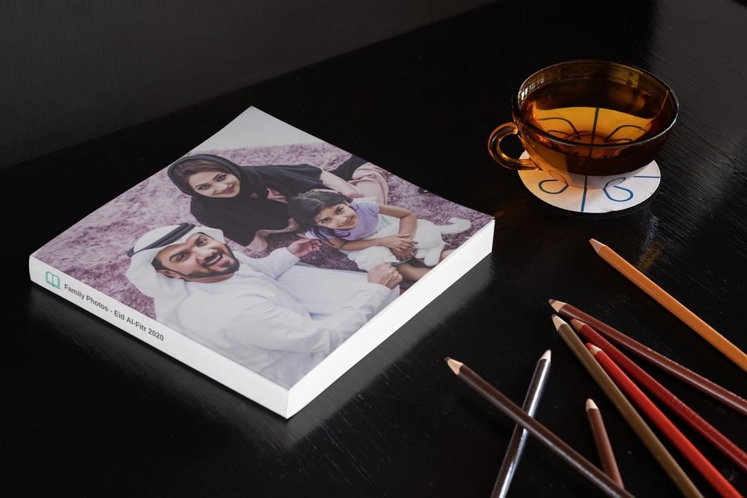 Image description: A photo of a family on the cover of a photobook. It is on a wooden table next to a cup and some colored pencils.