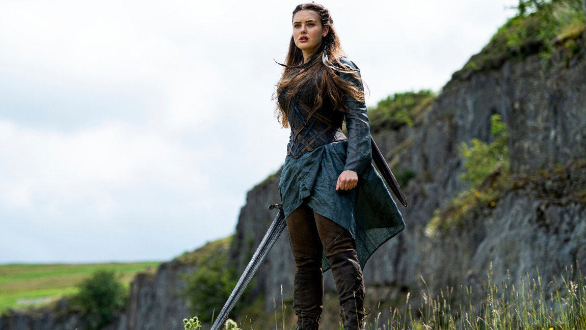 [Image description: A brown-haired girl, Nimue (Katherine Langford) stands tall in a valley with a massive sword in hand.] Via Netflix
