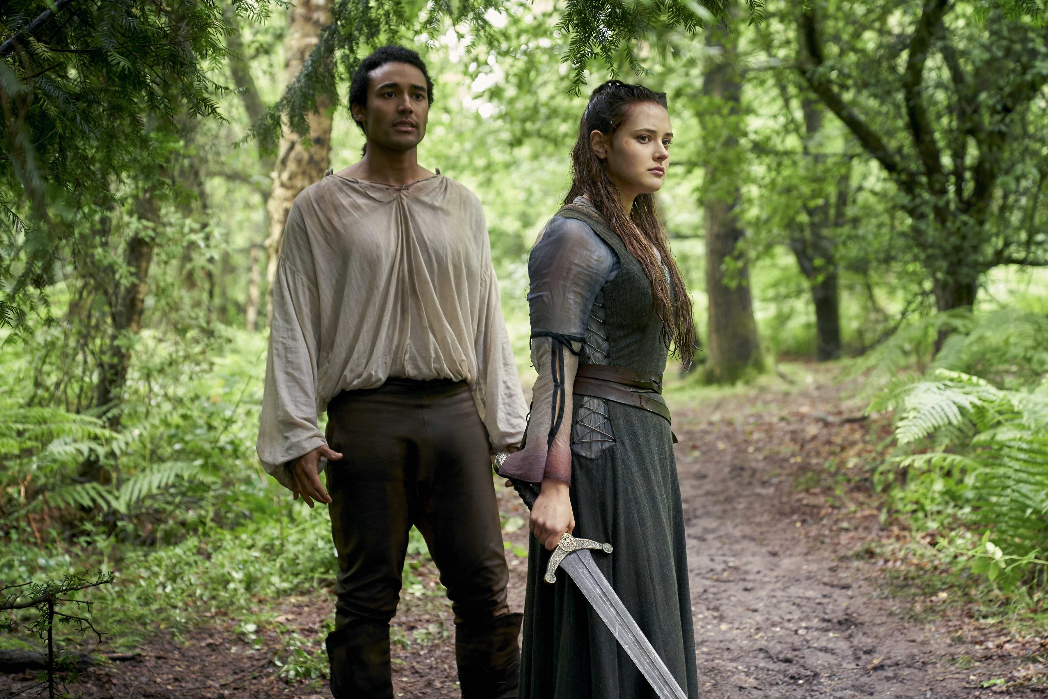 [Image description: Arthur and Nimue stand in a forest. She is holding the Sword of Power] Via Netflix