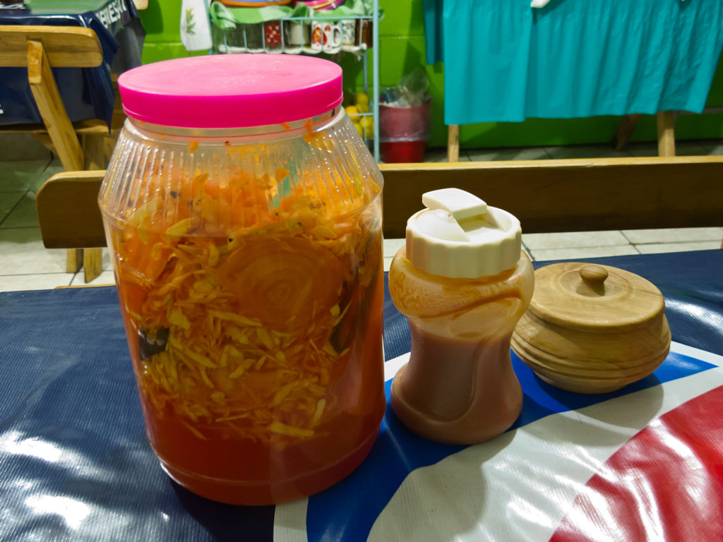 A Jar of curtido sits on a plastic tarp next to two sauce containers