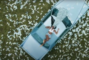 [Image Description: Flo Milli is lying on top of a car and money is dispersed across the ground. Flo Milli wears a long durag with a money design on it. Via WeUpOnIt.com