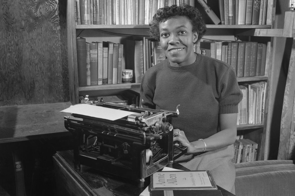 Gwendolyn Brooks in front of her typewriter and bookshelf.