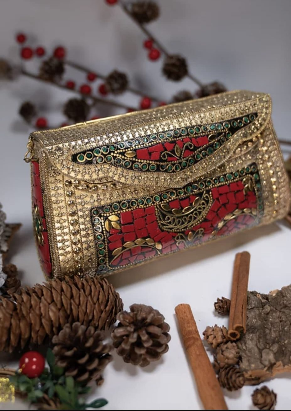 [Image Description: A gold and red metal clutch.] Via Oraniq Living