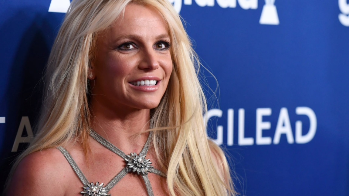 Britney Spears stands against a blue wall and smiles broadly.