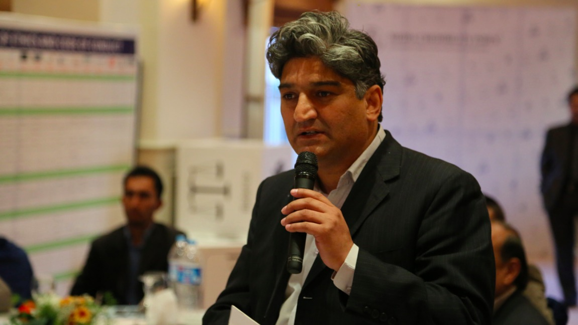 Journalist, Matiullah Jan, speaking in a mike. He has salt and pepper hair and he is wearing a black suit.