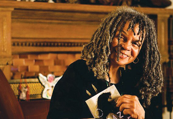 Poet Sonia Sanchez poses with a book in hand.