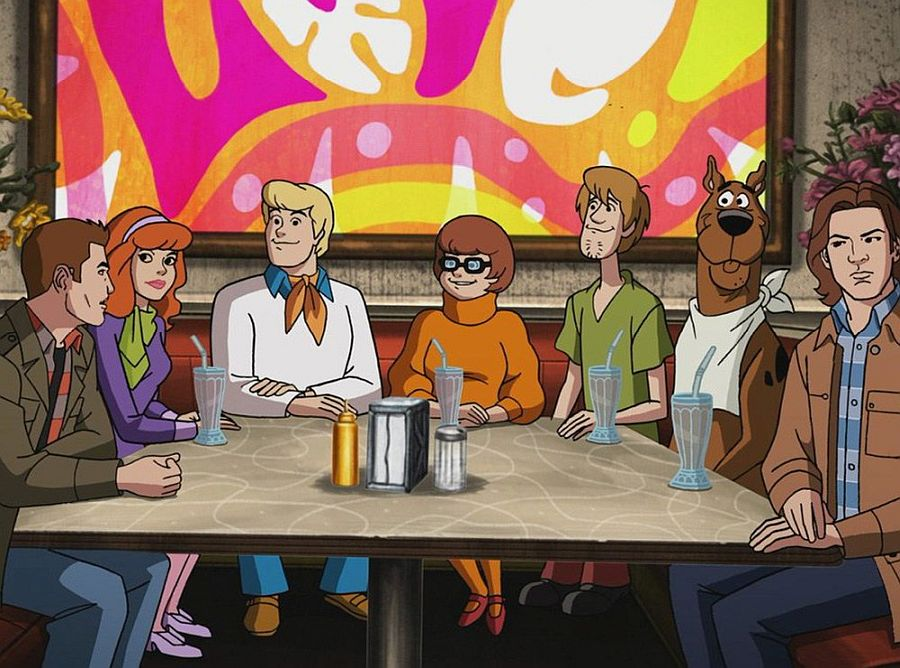 Still from Scoobynatural: A cartoon group of people and a dog sit around a diner table. Via thenerddaily.com