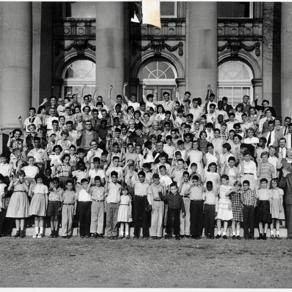 A large group of children is gathered on the steps of the Graham Windham orphanage. The children are of various ages. All the children have cheery expressions on their faces, and some are waving.