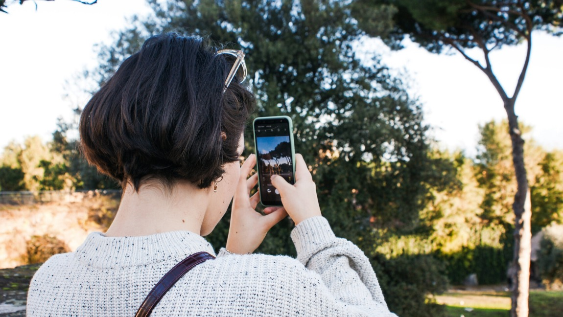 A woman holds her phone up, shooting a video.