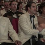 [Image description: Jeremy Pope, Darren Criss, and Laura Harrier as their Hollywood characters sitting in a theatre in formal wear, watching a movie.] Via LA Times