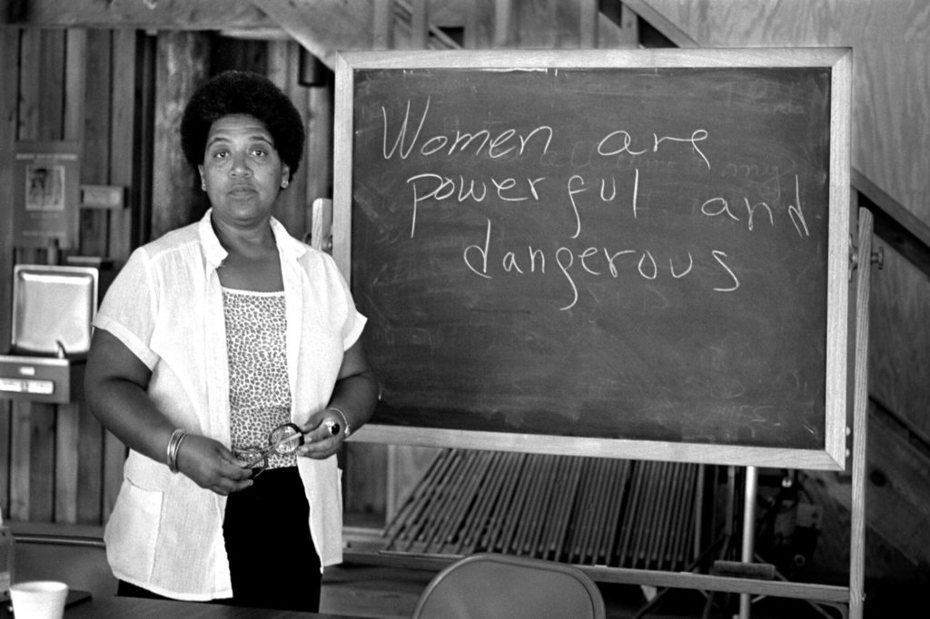 "Audre Lorde stands in front of a blackboard that reads ""women are powerful and dangerous."""